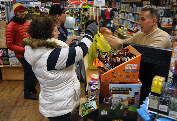 Legend-n-Heroes proprietor Neil Robichaud has his hands full during last Friday's Moonlight Madness shopping extravaganza. David F. Rooney photo