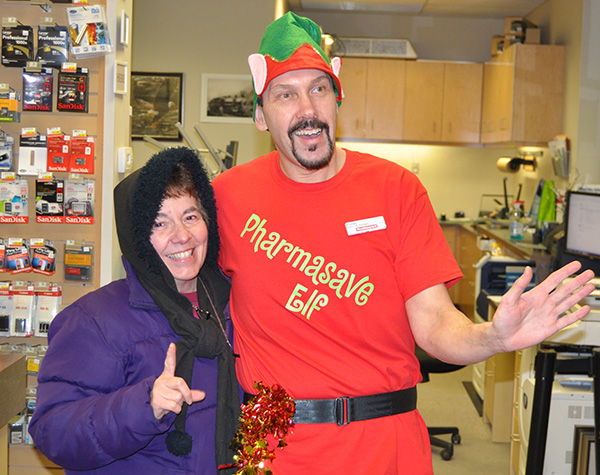 There's one in every crowd. Andrew Moore made a perfect, though somewhat taller-than-average, elf as he posed with shopper Rosemary Tracy at Pharmasave. David F. Rooney photo