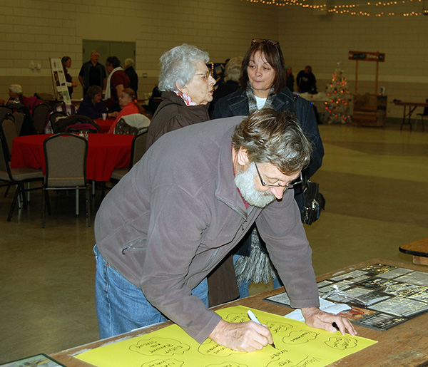 Brian Sumner of the BC Interior Forestry Museum and Discovery Centre whips up a quick sign for the museum's table at the fair. He looked surprisingly relaxed for someone who had just driven here from Vancouver. David F. Rooney photo