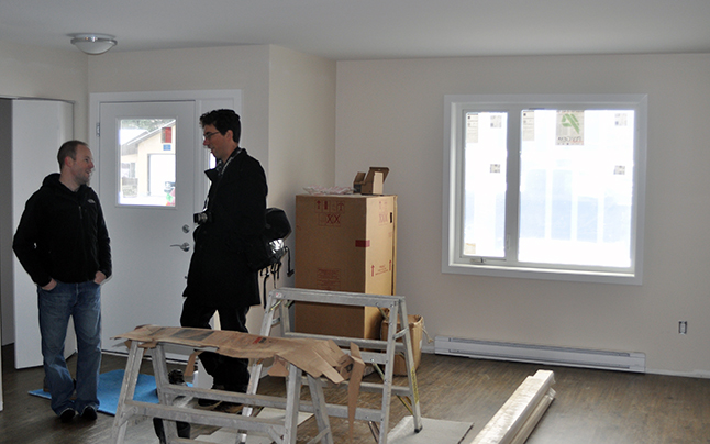 Mark Johnson (left), who accompanied his friend City Councillor Scott Duke on the media tour, talks with Review Editor Alex Cooper in the living room of one of the project's eight two-bedroom units. Workmen were completing the interior work when the tour was held. They should be done early in the New Year. The housing society is now accepting applications from prospective tenants. David F. Rooney photo