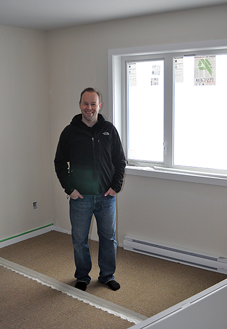Johnson poses in the master bedroom of the two-bedroom unit. There's no en-suite — in fact, each unit has only one bathroom — but there appears to be lots of closet space. David F. Rooney photo