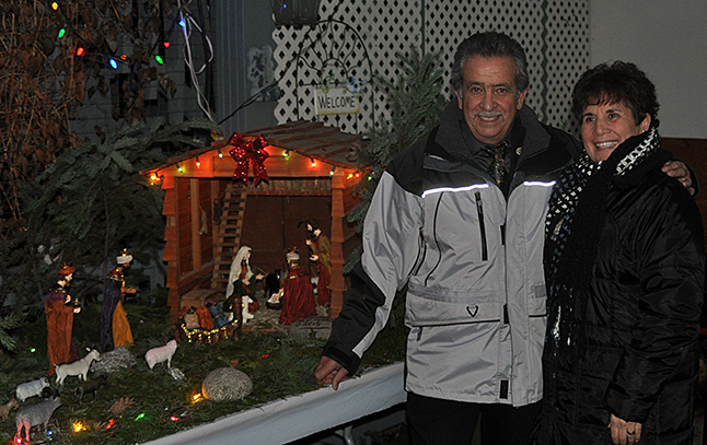 Paul and Cathy Suraci pose beside the elaborate Nativity Creche Paul has built in the carport of their home at 400 Townley. The couple finds joy in this simple acknowledgement of Christ's birth. Everyone is welcome to drop by to see the display. David F. Rooney photo