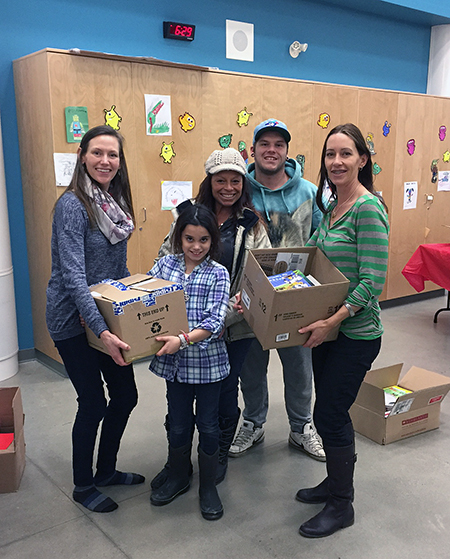 BVE parents Jocelyne Willms (left) and Bex Reid-Parkin (right) welcome Zoe Donovan, Lyssa Donovan and Tyler Donovan to select books on behalf of the Food Bank. Photo courtesy of Eleanor Wilson