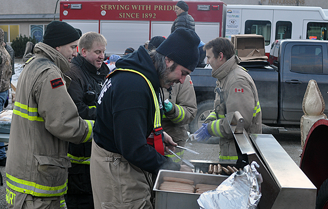 Glen Cherlet (center) leads a kind of double life. On the one hand he's the proprietor and all-around BBQ master at Begbie Barbeque and on the other he is also an active volunteer with the Revelstoke Fire Rescue Service. He got to put his culinary skills to good use grilling up hot dogs for sale at the Holiday Train event. David F. Rooney photo