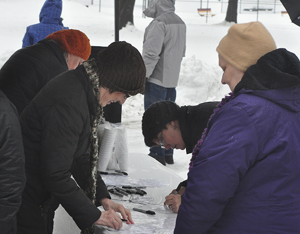 Ceremony participants write the names of the people who have vanished from their lives on individual snowflakes. David F. Rooney photo