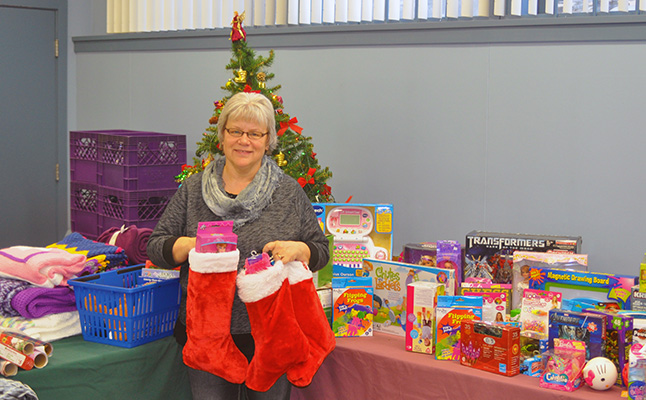 The annual Christmas Hamper Program is now up and running at the Food Bank! The program is sponsored by Community Connections and aims to help low-income families and seniors enjoy the festive season. Running the Food Bank and the program is a lot of work but Patti Larson, shown here surrounded by toys donated by Red Apple customers, blankets and holding three of the full Christmas stockings donated by Carol Deliver, blossoms at this time of year. David F. Rooney photo