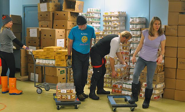 Their 10-minute coffee break over, the volunteers get back to work stacking the flats of canned foods that will help feed the needy in our city. David F. Rooney photo