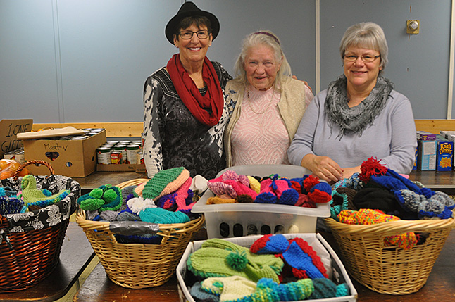 Carol Nakamoto and Edith Rudyk pose with Food Bank Manager Patti Larson and baskets filled with the 170 slippers, mitts and hats Edith knitted for Carol's annual Mitts for Kids Program. Edith is a prodigious and expert knitter who has been using the big needles to create woollens since she was six years old. The Mitts for Kids Program is Carol's own personal project. Every year she sets up donation jars at local businesses and solicits donations from the public. Her annual goal is $900 which finances Edith's efforts to produce hand-knitted wearables for boys and girls up to age 19 . This kind of home-grown program clearly shows that compassion is alive and well in Revelstoke. David F. Rooney photo