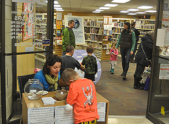 Assistant Librarian Gabriela Draboczi helps young boy sign in for the Carousel of Nations' interactive children's activities held in the library this year. David F. Rooney photo