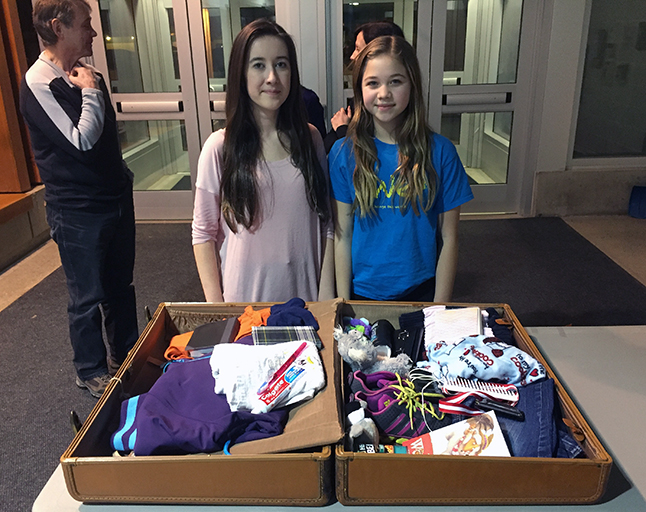 Beth Brodie and Kira Sawatzky, both Begbie View Elementary School Me to We Club members, put together this interesting suitcase full of items you might — maybe not — want if you had to flee from home. David F. Rooney photo