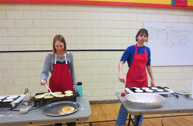 Student teacher Georgia Mackenzie (left) and Grade 5/6 teacher Michelle Gadbois cooking up some delicious pancakes. Todd Hicks photo. Caption by Emily Macleod, Amelie Delesalle and Rebecca Grabinsky
