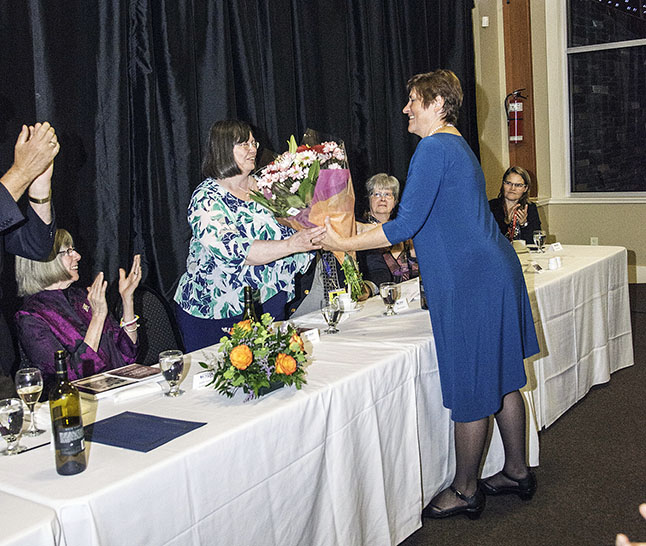 Jan Morehouse, president of the Revelstoke Museum and Archives Society, presenting Cathy English with a bouquet of flowers. Kip Wiley photo