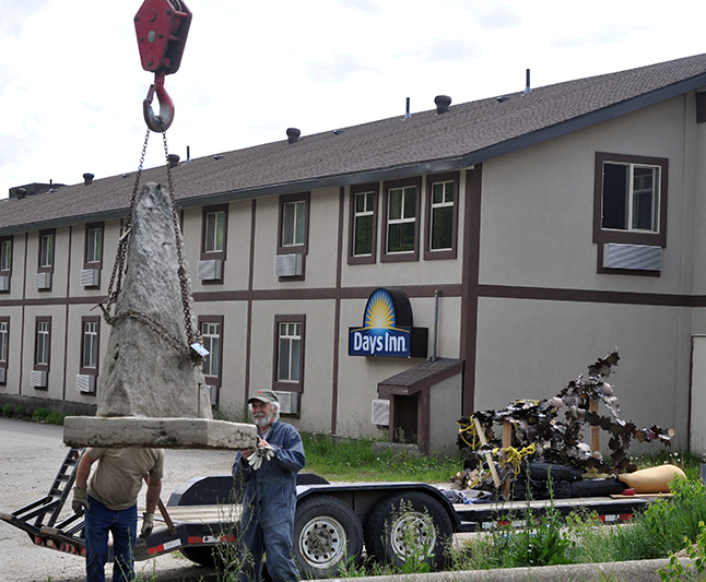 Artist John McKinnon delivered Revelstoke's newest piece of public art, a bronze statue titles Blowin' in the Wind, to its home at the Visual Arts Centre on Wilson Street on Friday, May 20. A mobile crane hoisted the stone base as well as the sculpture's two parts onto spot in The Centre's colourful public garden. David F. Rooney photo