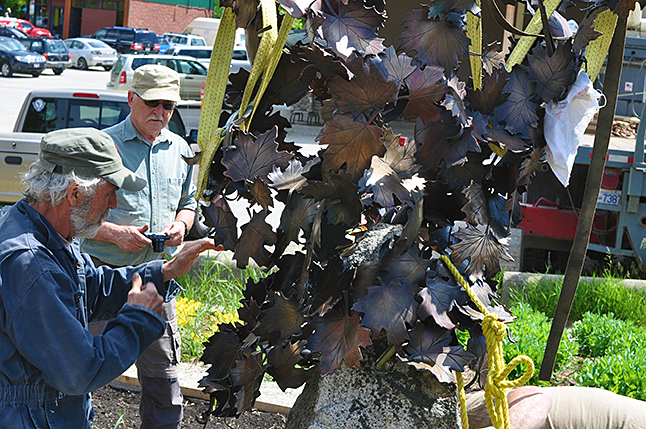 McKinnon checks the stability of the piece, which was inspired by the way autumn winds sometimes cause leaves to swirl into the air.  David F. Rooney photo
