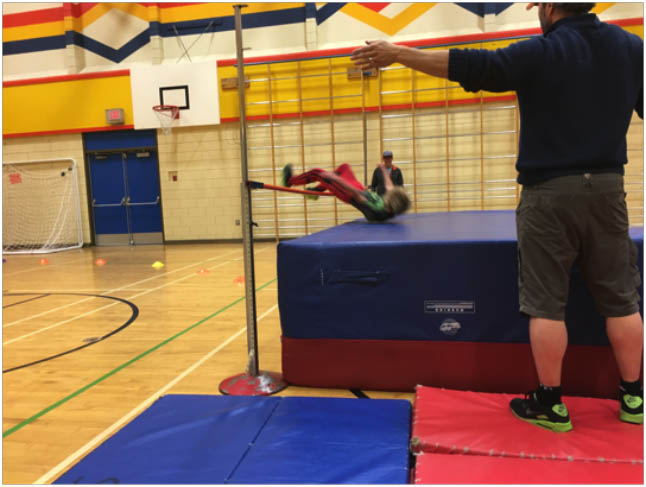 This is Ryder Ray doing high jump in the gym. Photo by Todd Hicks. Caption by Emily MacLeod, Amelie Delesalle and Rebecca Grabinsky