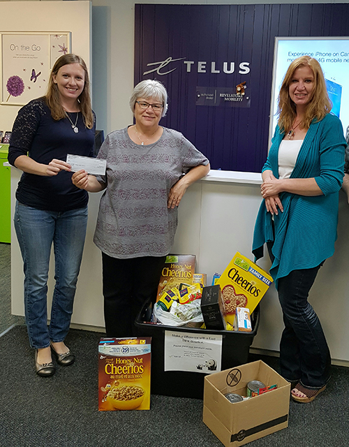 Revelstoke Mobility's Shannon McKee helped Telus mark its tenth annual Days of Giving program by presenting Patti Larson of the Community Connections Food Bank with a $1,000 cheque on Monday, June 13, as Chantal Mercer looks on. The company's philanthropic program brings together more than 17,850 volunteers at over 1,350 activities across Canada from May 16 until June 14 each year. Photo courtesy of Revelstoke Mobility