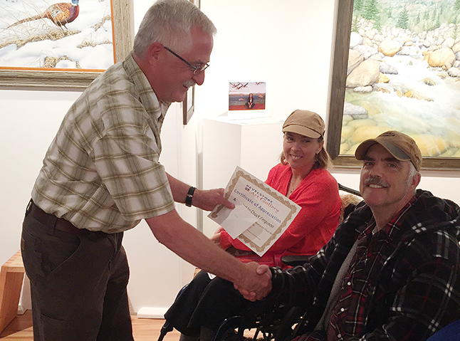 Visual Arts Society Chairman Ken Talbot presents Chuck Ferguson with a certificate of recognition for all his volunteer work at the Visual Arts Centre during the society's AGM on Wednesday, June 15, as Pauline Hunt looks on. Chuck donates hundreds of hours each year doing maintenance and odd jobs. David F. Rooney photo