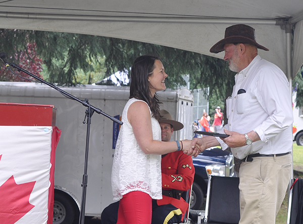 Canada Day organizer Megan MacIsaac presents George Buhler of the Rod & Gun Club with the plaque for Best Float in the parade. David F. Rooney photo