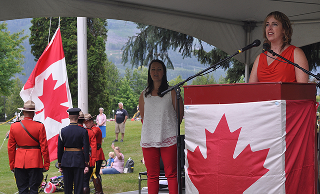 Charlene Foisy leads the crowd in singing O Canada as a detail of Mounties raise the flag. David F. Rooney photo