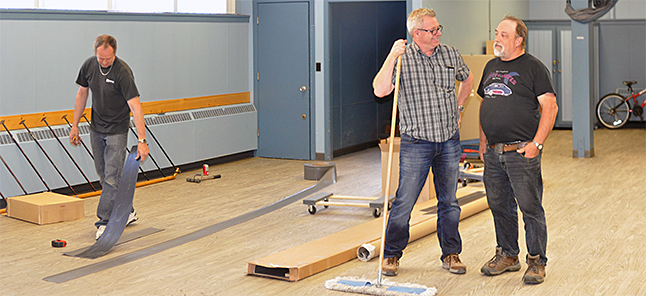 Royal Canadian Legion President Ed Koski (right) drops in at the Food Bank, located in the Legion's basement this week to check on a project to replace the space's tired green linoleum with new composite flooring installed by Revelstoke Flooring's John Kehler (center) and Dwayne Campbell. David F. Rooney photo