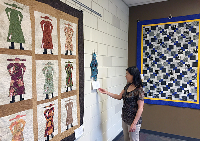Community Librarian Kendra Runnalls admires some of the creations by Revelstoke Quilting Guild members that are now on display at the public library. David F. Rooney photo