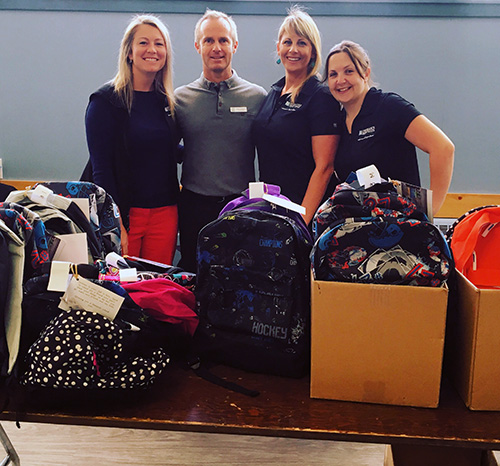 "Amanda Rota, Jamie Hobgood, Erin Russell and Emily Horkley pose with some 9f the backpacks that were purchased by RCU staff for distribution by the Community Connections' Food Bank last Friday. Every year the Credit Union staff generously donate backpacks and school supplies to children whose families attend programming with Community Connections. Since 2002 they have helped 625 children in need and they fundraise as a group to ensure each child has a backpack that is age appropriate and it is filled with the necessary school supplies. ""I always jump at the chance to volunteer and appreciate the eye-opening experience it is for others who haven't been in to the food bank previously. You and your team provide such a valuable service to the community of Revelstoke and I know that we at RCU are happy to contribute however we can. I look forward to seeing you at the Emergency Services Food Drive and I've begun soliciting volunteers at RCU and RCUI for September. Photo courtesy of the Revelstoke Community Connections Food Bank"