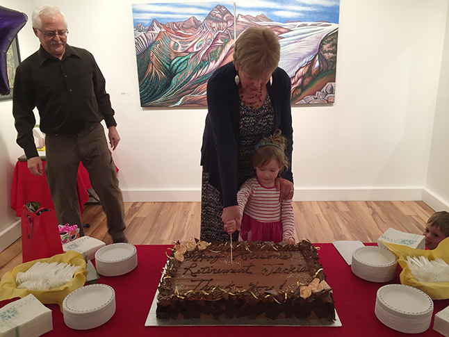 Jackie, assisted here by her granddaughter Isobel, manages t cut the magnificent retirement cake. David F. Rooney photo